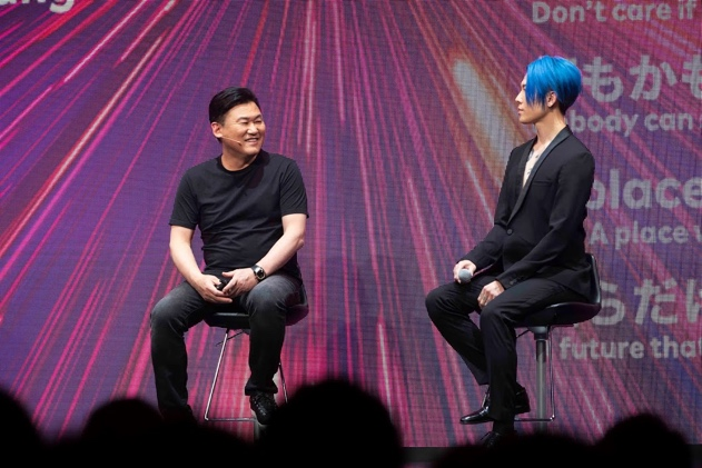 "Rakuten CEO Mickey Mikitani (left) chats with MIYAVI at a March 3 press conference for the launch of Rakuten Mobile's inaugural mobile phone plan ""Rakuten UN-LIMIT."""