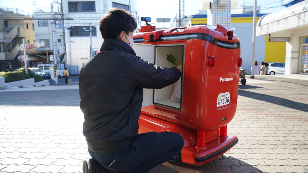 A Seiyu supermarket employee loads groceries into the Rakuten UGV.