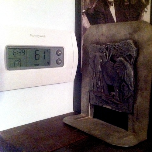 Thermostat showing temperature of 61 degrees F