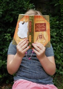 Child reading The Wilderking Trilogy: The Bark of the Bog Owl
