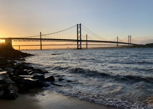 The Forth Road Bridge is seen silhouetted against a sunset sky. Waves are breaking against the shore.
