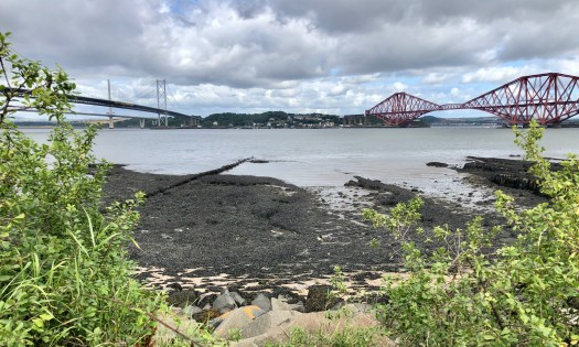 Views across a rocky outcrop into the Firth of Forth - The Binks. The Forth Bridge and Forth Road Bridge can be seen, and beyond them is the Fife coast.