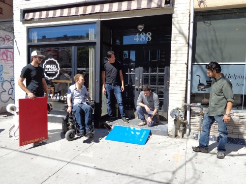 Group standing in front of local business with wheelchair ramps