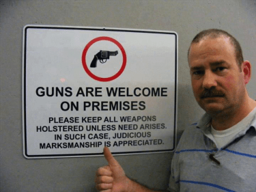 """Man stands approvingly beside sign which reads, """"Guns are welcome on premises. Please keep all weapons holstered unless need arises. In such cases, judicious marksmanship is appreciated."""""""