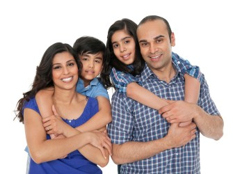 Indian family portrait. Happy parents piggybacking their children over white background. Horizontal Shot.