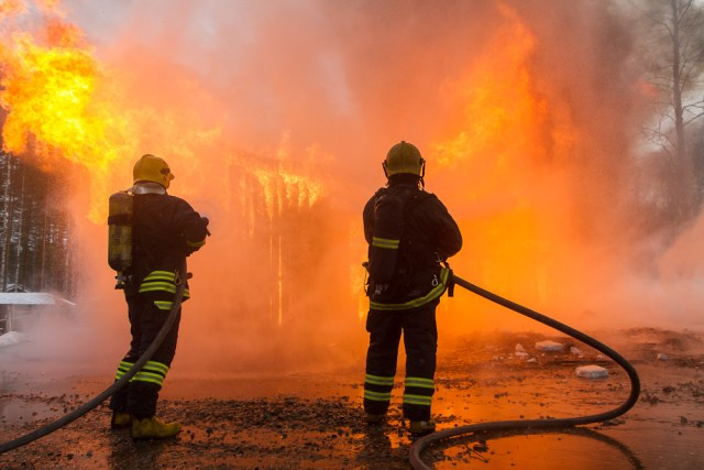 firefighters with houses outside of a burning house