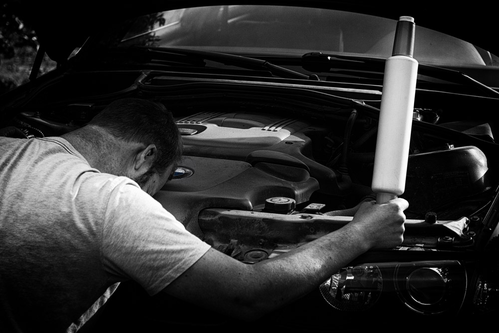 a man with a dough roller sitting in front of open hood of car