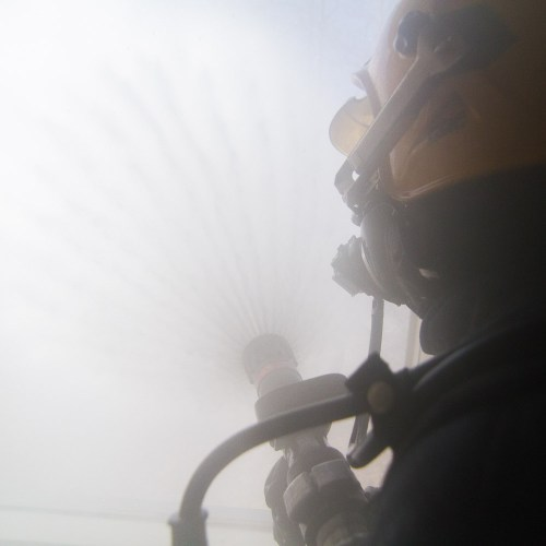 firefighter ventilating smoke out of structure
