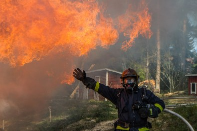 firefighter posing in front of flames