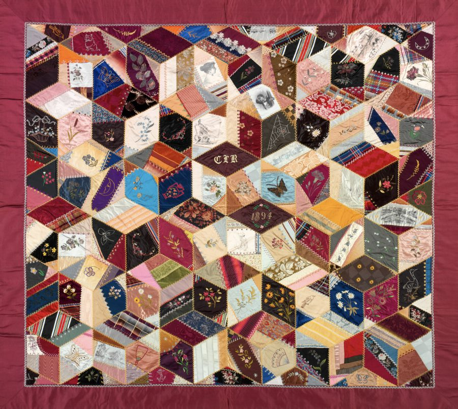 1894 crazy quilt by Clara Louise Roscoe, donated by family to The Metropolitan Museum of Art, public domain image, dominant color is deep purplish red, including border, with unpredicatable square and diamond patches in red, blue, yellow, pink, dark gray or black, and cream