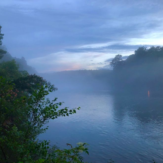Chattahoochee River with smooth water and a lantern glowing on a bankside