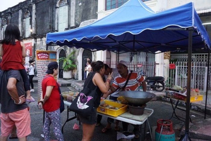 Inês comprando dos empanadillas en Armenian Street
