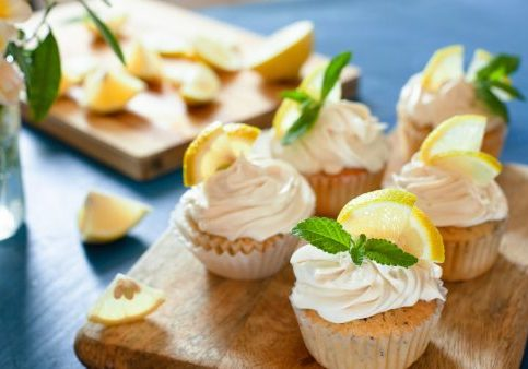 Lemon cupcakes with poppy seeds, white butter cream and  slice of lemon on blue background, selective focus