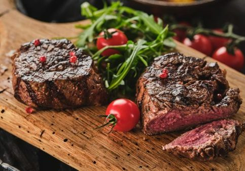 Grilled fillet steaks on wooden cutting board. Succulent thick juicy portions of grilled fillet steak served with tomatoes and roast potatoes on an old wooden board