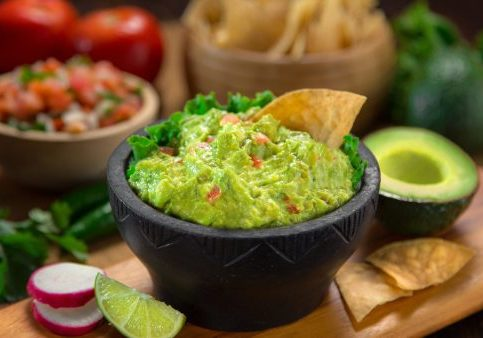 A delicious Bowl of Guacamole next to fresh ingredients on a table with tortilla chips and salsa