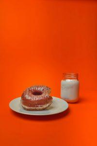 Randy's glazed donut on a plate beside a mason jar full of milk