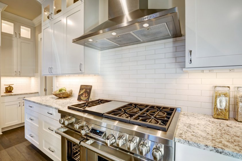 Beautiful kitchen features a nook filled with steel stove
