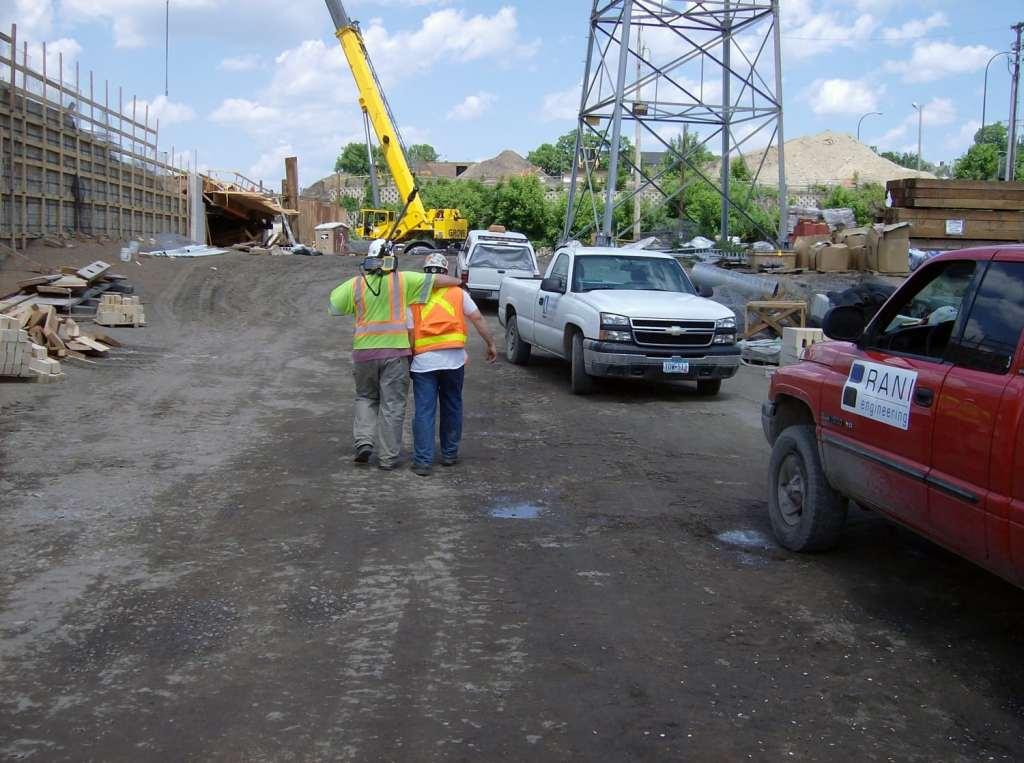 2 survey technicians walking on construction site
