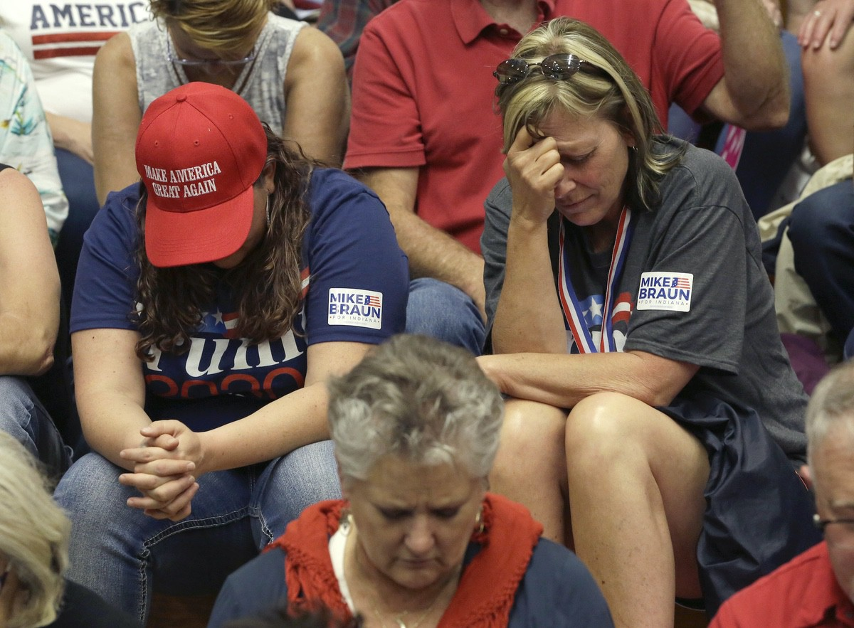 President Donald Trump supporters bow their heads and pray before a campaign rally Thursday, May 10, 2018, in Elkhart, Ind. (AP Photo/Charles Rex Arbogast)