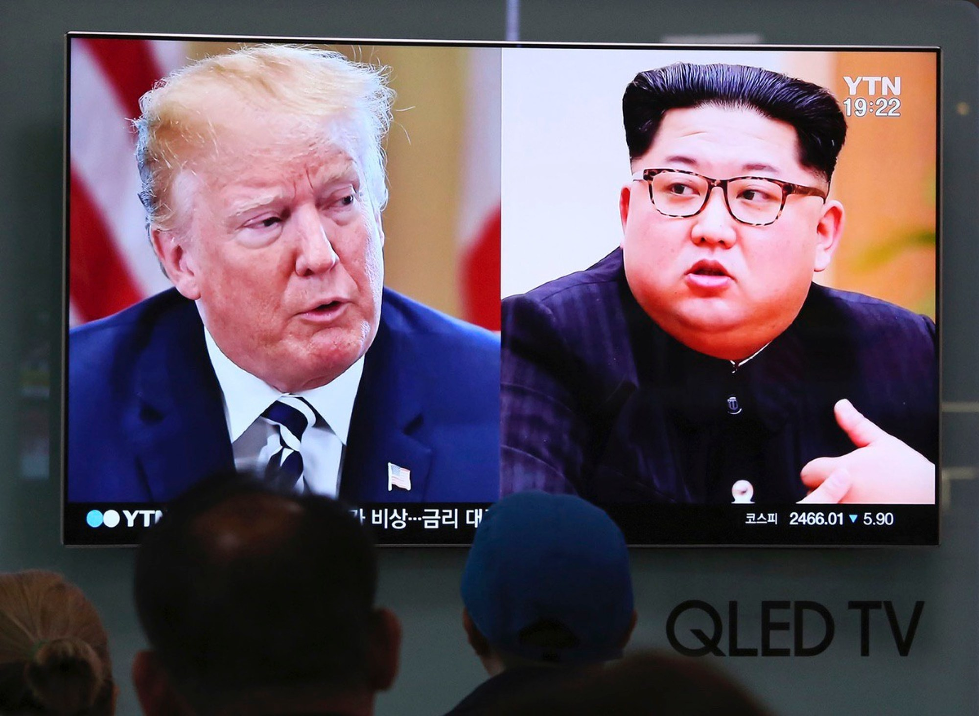 People watch a TV screen showing file footage of U.S. President Donald Trump, left, and North Korean leader Kim Jong Un during a news program at the Seoul Railway Station in Seoul, South Korea, Thursday, May 24, 2018. (AP Photo/Ahn Young-joon)