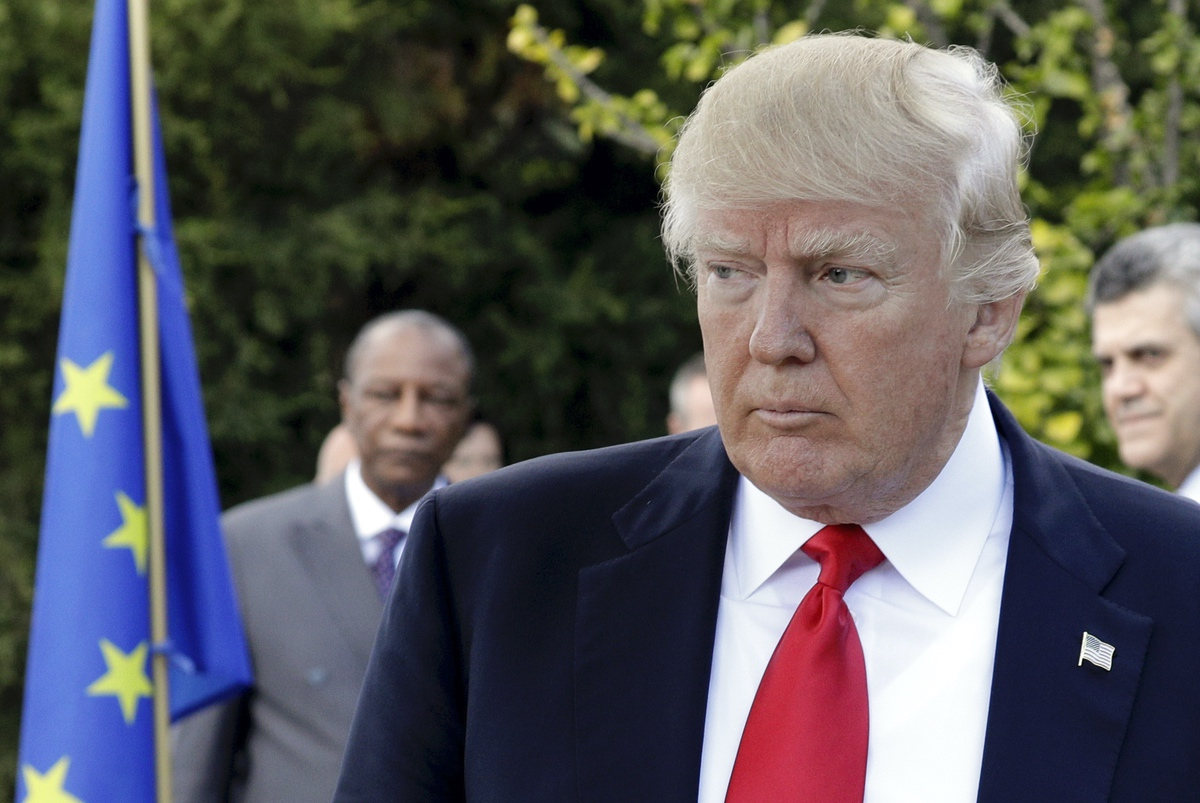 U.S. President Donald Trump walks past the European Union flag at the G7 session in the Sicilian town of Taormina, Italy, Saturday, May 27, 2017. (AP Photo/Andrew Medichini)