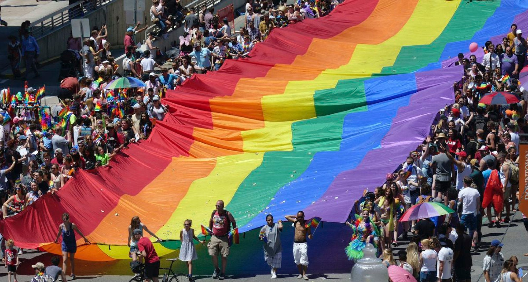 People carry a flag during the Utah Pride parade in Salt Lake City. Salt Lake City police are looking for leads after a man was allegedly attacked while trying to defend two gay men being chased after the Utah Pride Festival. Sunday, June 3, 2018 (AP Photo/Rick Bowmer)