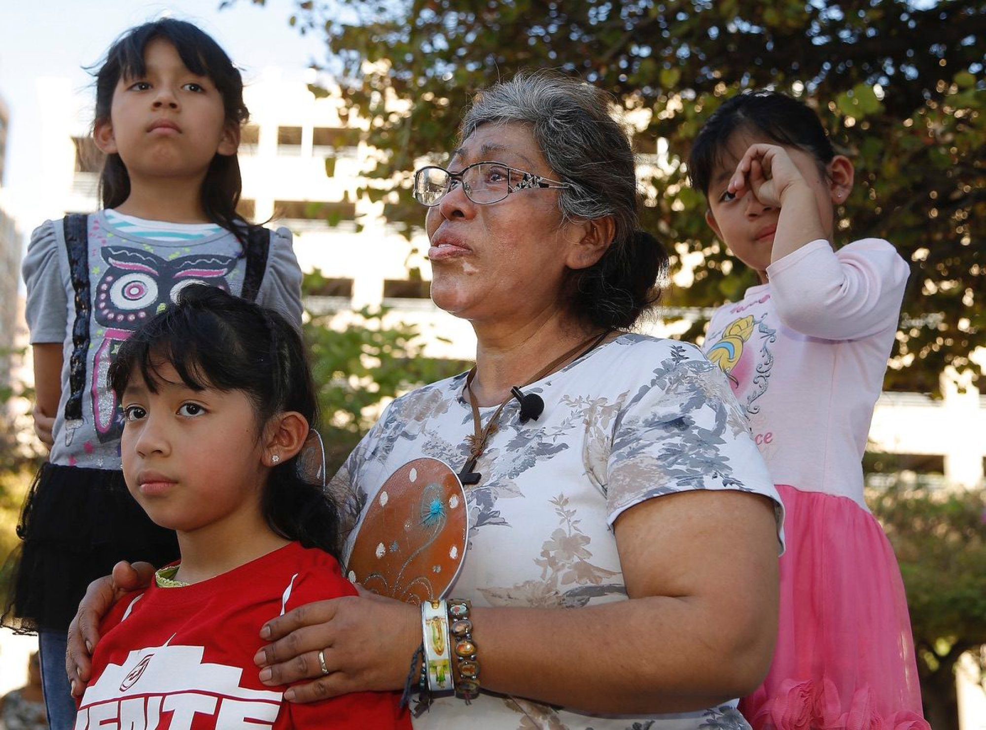 Lucia Ajas, middle, talks about her and her children, Regina Vargas, 7, left, Akemi Vargas, 8, second from left, and Trinidad Vargas, 5, right, being separated from their father during an immigration family separation protest in front of the Sandra Day O'Connor U.S. District Court building, Monday, June 18, 2018, in Phoenix. (AP Photo/Ross D. Franklin)