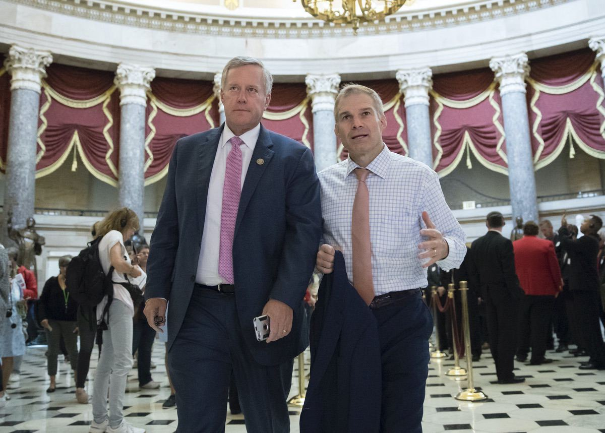 Rep. Mark Meadows, R-N.C., chairman of the conservative House Freedom Caucus, and Rep. Jim Jordan, R-Ohio, a key member of the group, walk through Statuary Hall at the Capitol in Washington, Wednesday, Sept. 13, 2017. (AP Photo/J. Scott Applewhite)