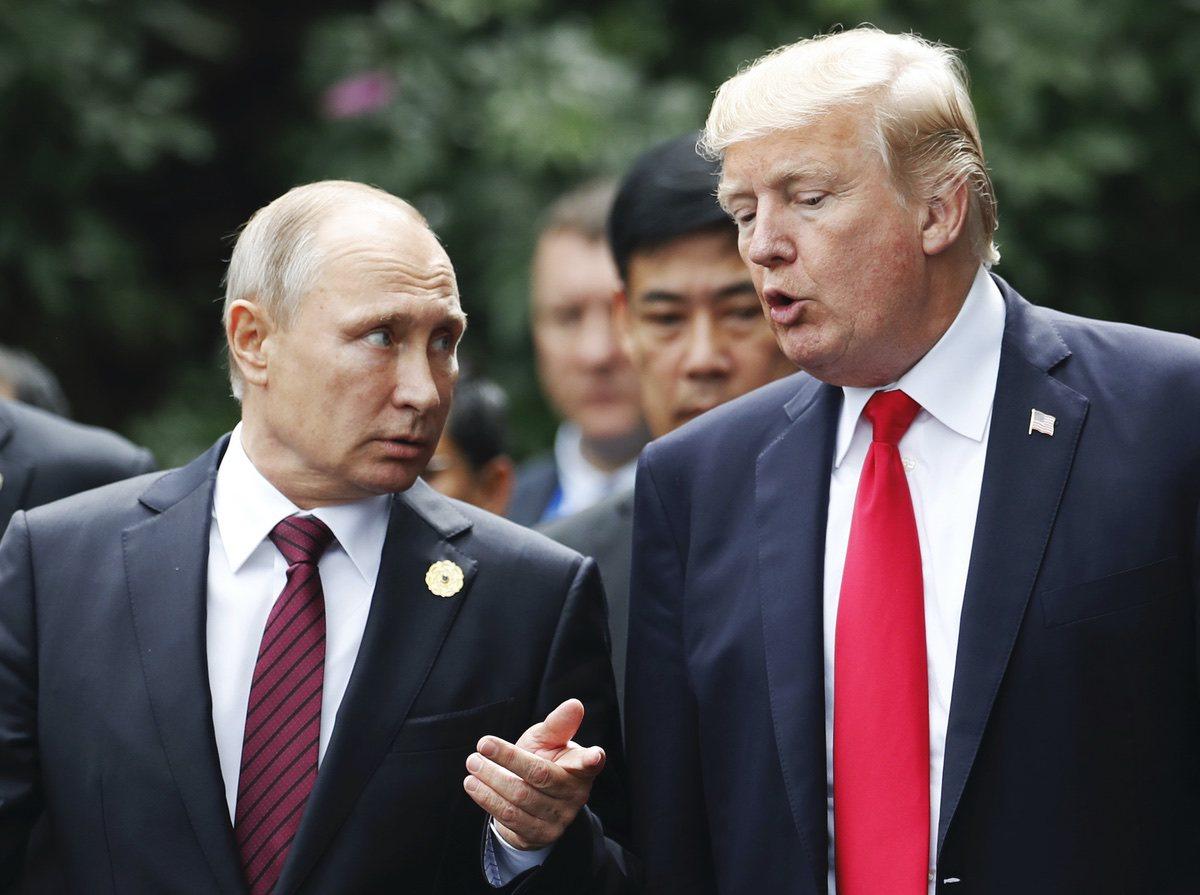 U.S. President Donald Trump and Russia's President Vladimir Putin talk during the family photo session at the APEC Summit in Danang, Vietnam, Saturday, Nov. 11, 2017. (Jorge Silva/Pool Photo via AP)