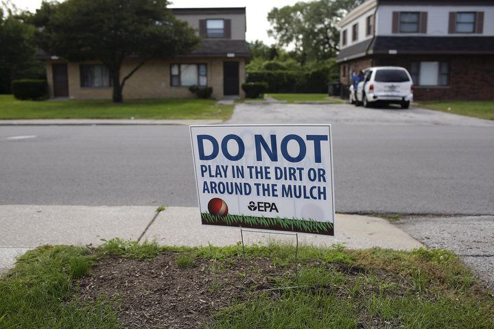 A sign at the West Calumet Housing Complex warns residents not to play in the dirt or around the mulch because of the lead in the soil. (Color Lines)