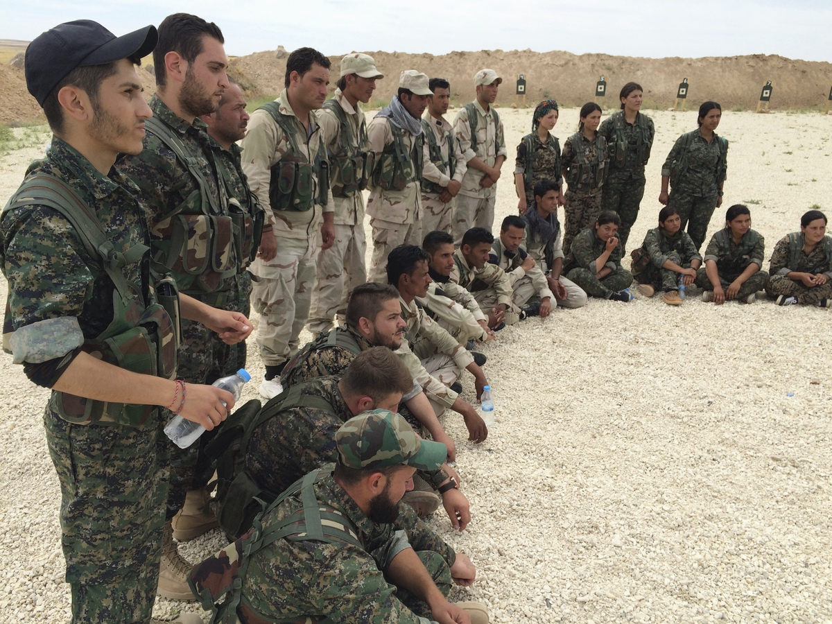 Members of what the U.S. calls the Syrian Democratic Forces gather after a training session at a firing range in northern Syria. In this file photo taken. May 21, 2016 (AP Photo/Robert Burns)