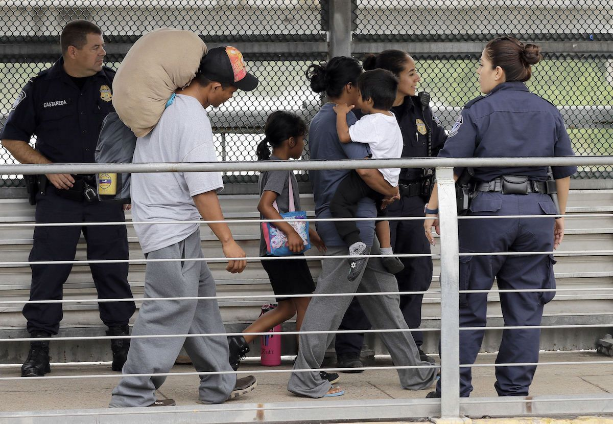 Ever Castillo, left, and his family, immigrants from Honduras, are escorted back across the border by U.S. Customs and Border Patrol agents Thursday, June 21, 2018, in Hildalgo, Texas. The parents were told they would be separated from their children and voluntarily crossed back to Mexico after trying to seek asylum in the United States. (AP Photo/David J. Phillip)
