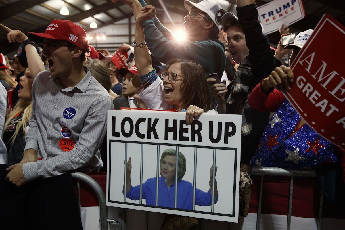 """Supporters of Donald Trump, one holding a sign that reads, """"LOCK HER UP,"""" cheer during a campaign rally in Leesburg, Va - Monday, Nov. 7, 2016 (AP Photo/ Evan Vucci)"""