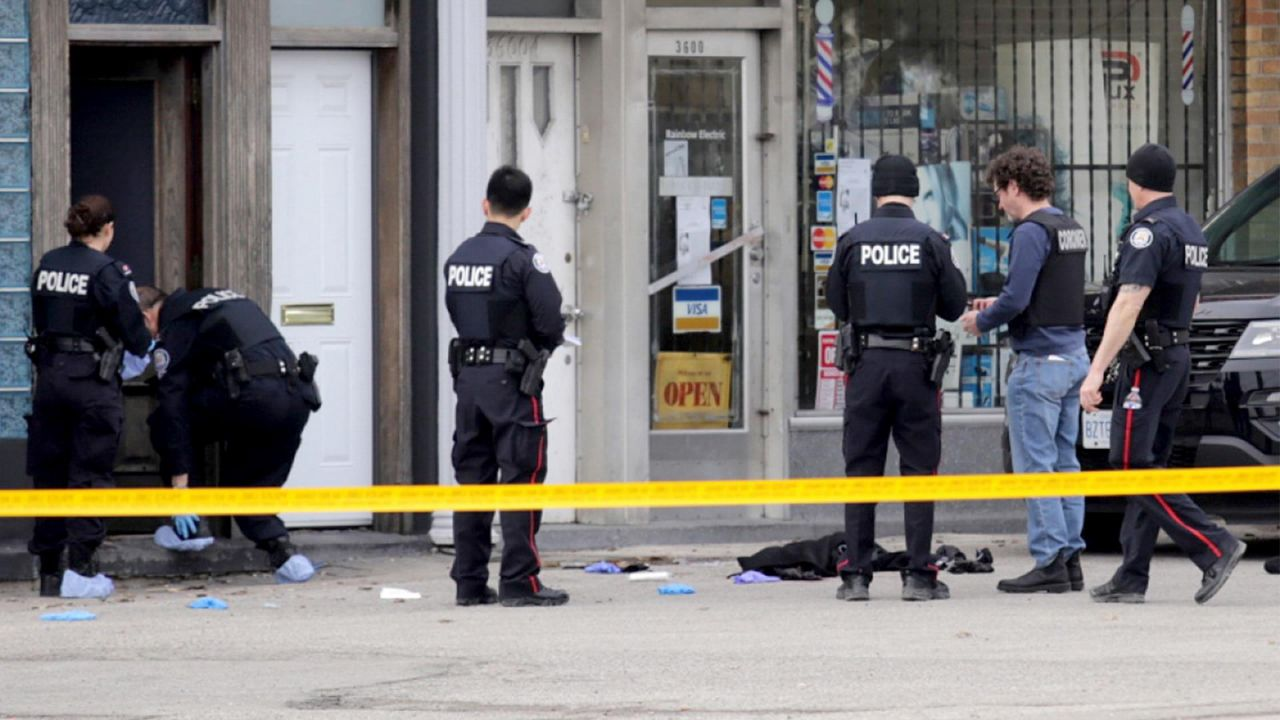 Toronto police officers stand outside a business in North York where one woman died and two other people, a man and woman, were injured in a stabbing on Monday afternoon. A 17-year-boy has been charged with first-degree murder and attempted murder. (Michael Cole/CBC)