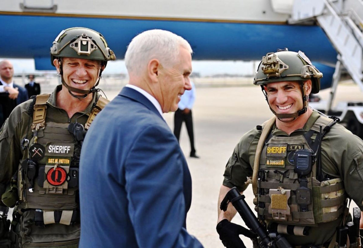 "Vice-President Mike Pence posing with members of the Broward County, Florida SWAT team, one of whom is wearing a patch of the ""QAnon"" far-right conspiracy theory movement – November 30, 2018. (White House employee; cropped by Beyond My Ken)"
