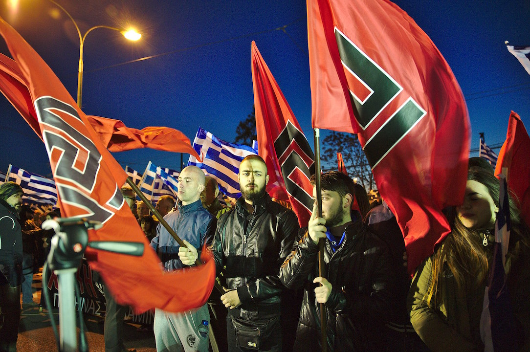 Neo-Nazi Golden Dawn members hold flags with the meander symbol at a rally outside of party HQ, Athens, March 2015. Earlier this year, leaders of Golden Dawn were convicted for running an organized crime group. (DTRocks, CC BY-SA 4.0 via Wikimedia Commons)