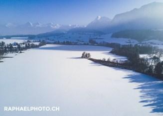 Zugeschneiter Amsoldingersee mit den Berner-Oberländer-Bergen im Hintergrund