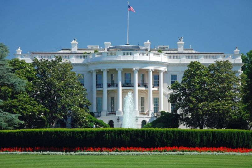 Languages of the United States: A North façade of the White House on a sunny day, surrounded by trees and bushes