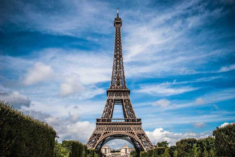 Dialects of French: a slight worm's eye view of the Eiffel Tower surrounded by trees on a sunny, yet cloudy day