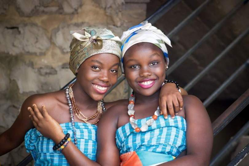 Languages of Africa: Two African girls sat hugging each other and smiling in a brick building