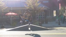 A skateboarder attempts a trick in front of Au Bon Pain