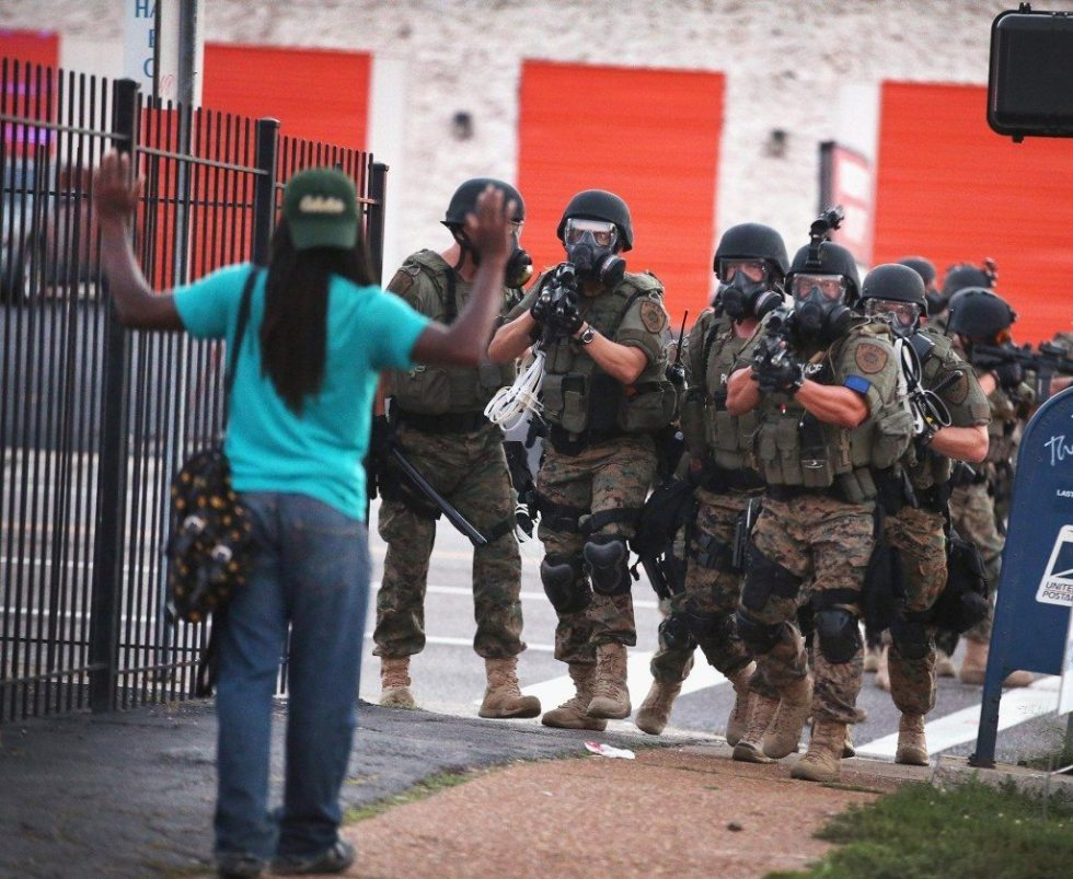 An Armed Police Unit challenges a passerby in Ferguson.