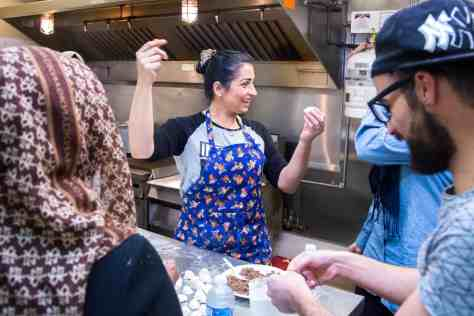 Lila, who immigrated from Syria 11 months ago, leads this week's class. She breaks into a song and dance while she teaches the group to cook traditional Syrian food. Lila wants to open her own restaurant in Edmonton.| Rebecca Lippiatt