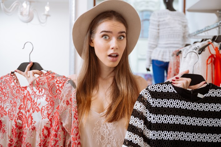 Confused woman doing shopping and choosing dress in clothing store