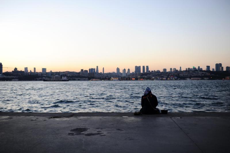 Eine Frau sitzt am Pier und schaut auf den Bosporus