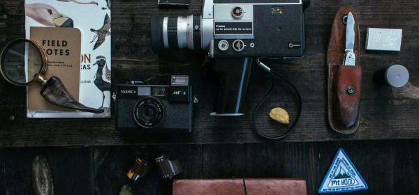 retro cameras near knife and lens near film on desk