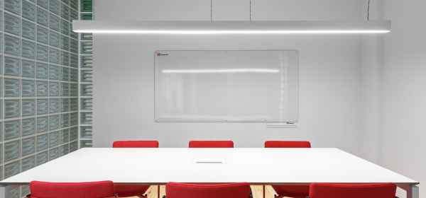 light room with table and chairs near whiteboard