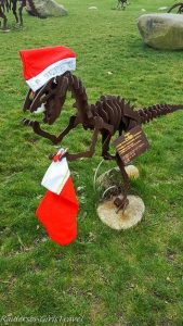 Metal Velociraptor statue decorated for the holidays at Dinosaur Farm in Coloma, Michigan