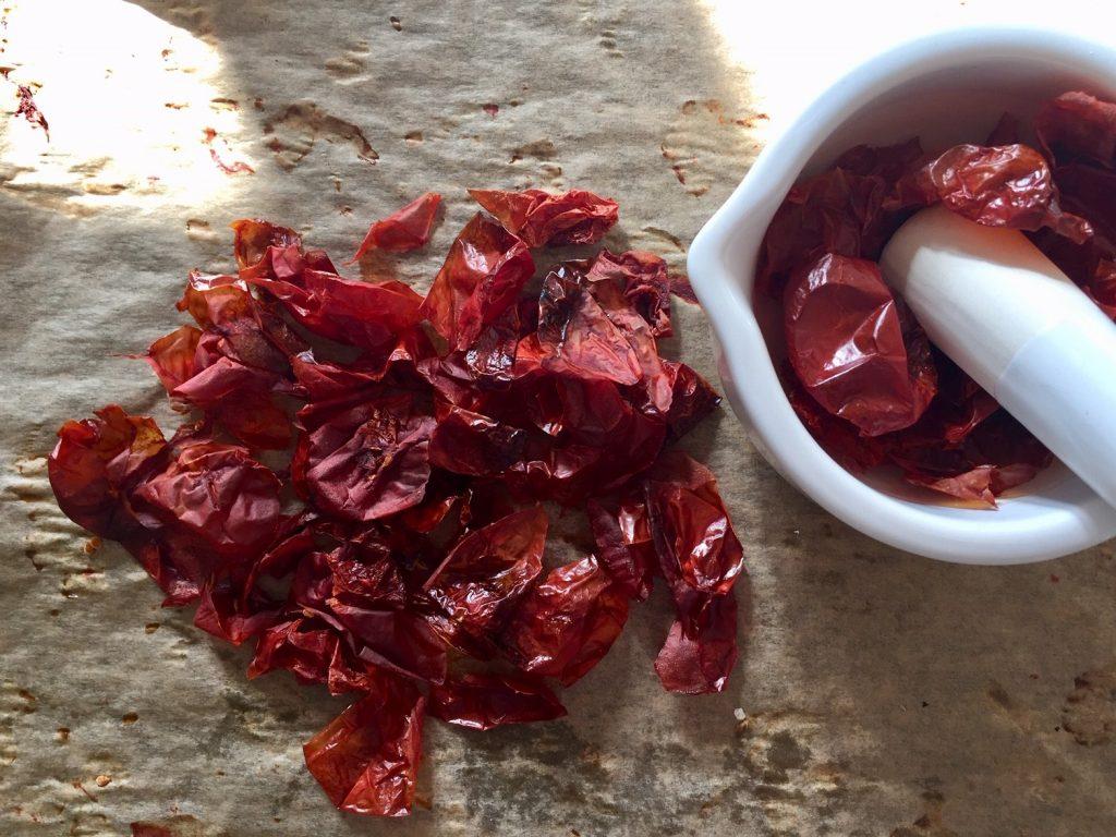 Tomatenhaut wird im Mörser zu Pulver