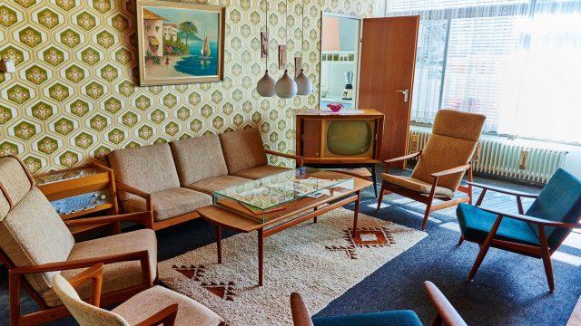 Wohnzimmer der 1965er Jahre mit Sofa, Fernseher, Tisch, gemusterter Tapete und Bild mit südländischem Motiv.